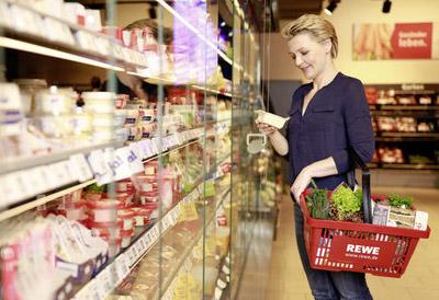 Жена пазарува в супермаркет REWE Group