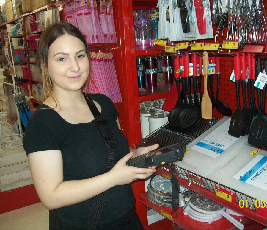 Жена държи баркод скенер в The Reject Shop