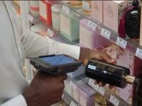 Служител на National Pharmacies сканира продукт с мобилен компютър