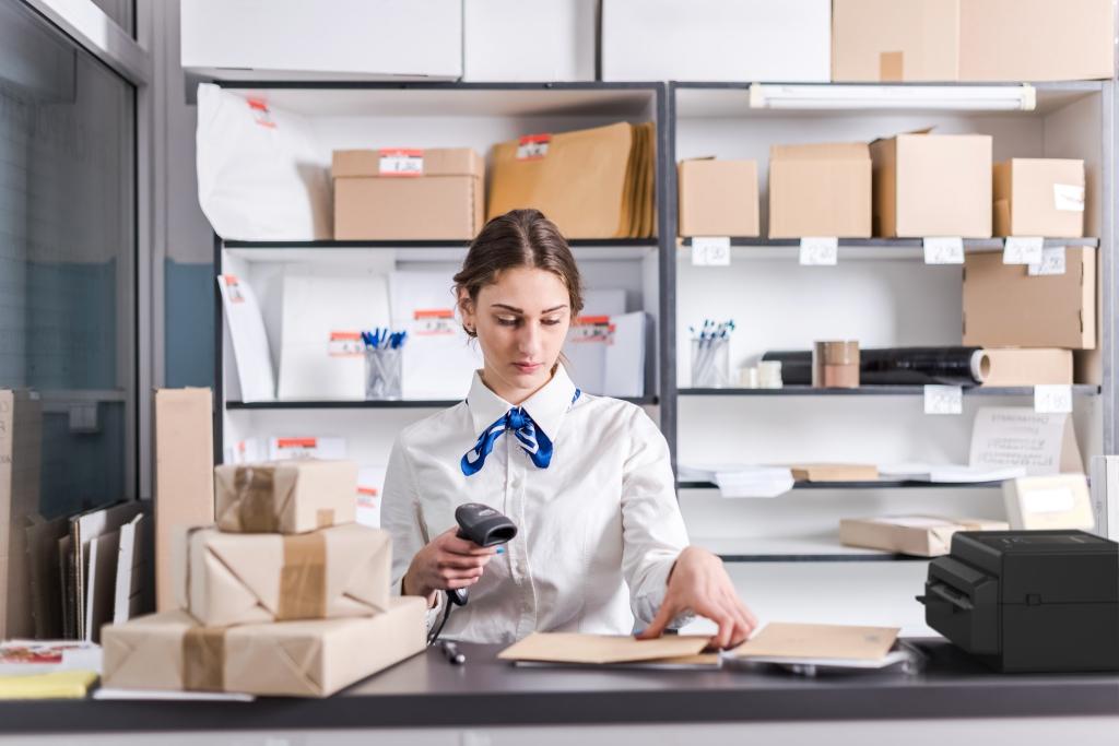 Жена сканира пакети в офис на спедитор - употреба на настолни баркод принтери Toshiba серия BV400D в логистиката