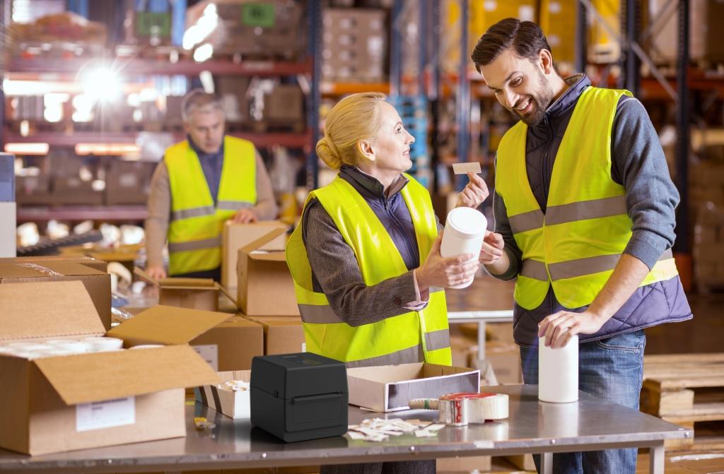 Работници в склад облепят продукти с етикети - употреба на настолни баркод принтери Toshiba серия BV400D в производството