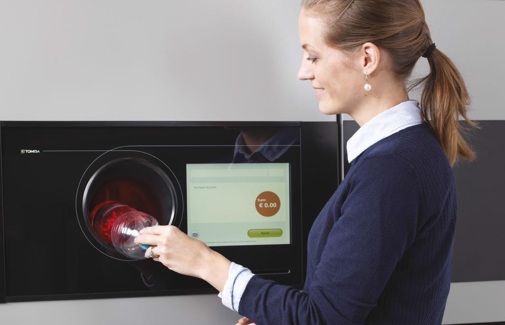 Жена използва вендинг машина за рециклиране