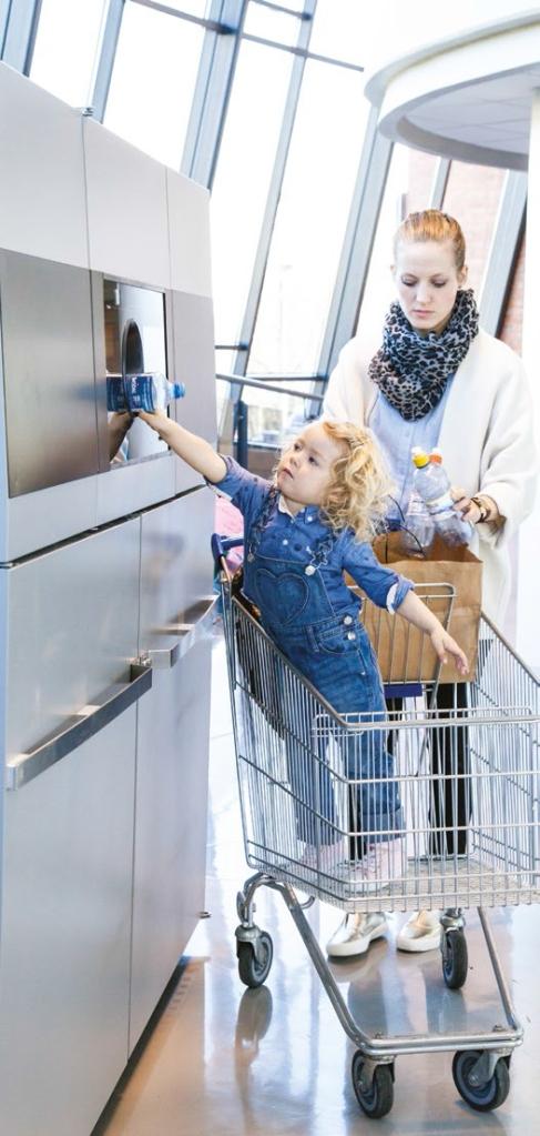 Жена и дете използват вендинг машина за рециклиране